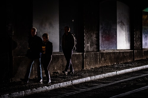 Three people walking under a dark bridge