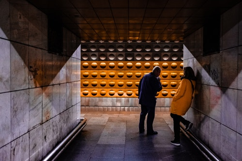 Patterns on the subway wall, with travelers in front
